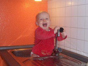 Baby sittzt in der Spühle und hat den Stöpsel entdeckt